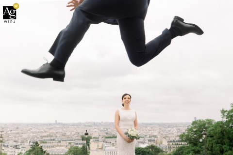 Montmartre, Paris, France wedding couple artistic image session showing the Bride standing 3-4 steps down the stairs and laughing while the groom is jumping on top of the hill