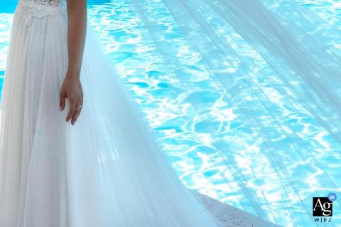 Ricevimento, Villa Eden, Bagnolo San Vito, Mantoue, Italie photo de détail de mariage de style artistique créée en attendant le gâteau, une partie de la robe et du voile avec un fond de piscine