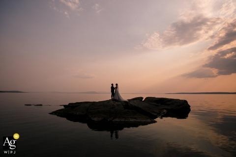 Sessione di immagini artistiche degli sposi di Yellowstone con la sposa e lo sposo su una mini isola al tramonto