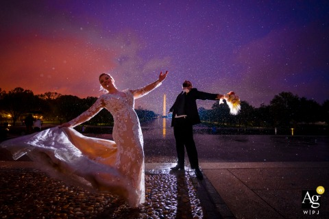 Lincoln Memorial, Washington DC wedding couple artistic image session as Bride and Groom rejoice in the rain at the Lincoln Memorial, with the Washington Monument in the background