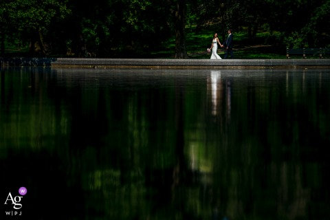 Central Park, New York City, New York wedding couple artistic image session as A bride and groom walk together around the pond