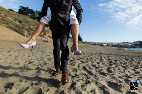 San Francisco artful style wedding detail picture of the groom carrying the CA bride piggyback in the sand