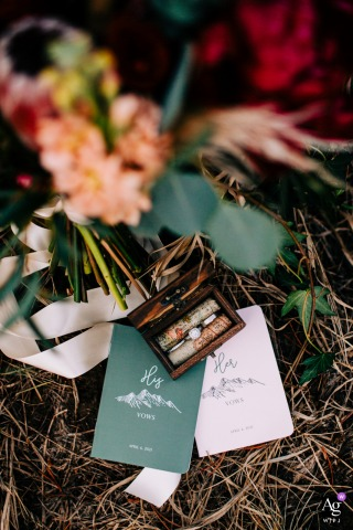 Colorado artful style wedding detail Photo of brides flowers, their rings, and vow books