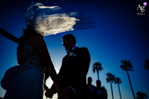 View thisdramatic McCormick Ranch Golf Club Scottsdale wedding veil blowing in wind during ceremony image, which was a featured pictureamong the best wedding photography in Arizona from the WPJA