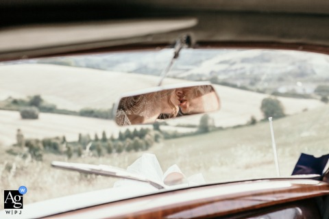 View thisimaginative Cesena wedding pic that was reflected in the vintage car mirror, a stolen kiss, which was a featured pictureamong the best wedding photography in Italy from the WPJA