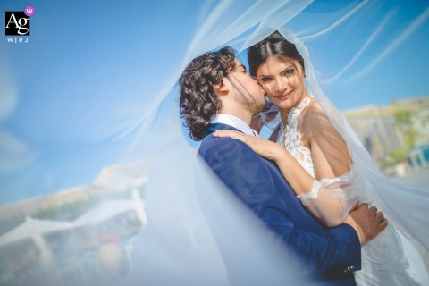 View thisstylish Siracusa bride and groom portrait under her veil and blue skies, which was a featured pictureamong the best wedding photography in Italy from the WPJA