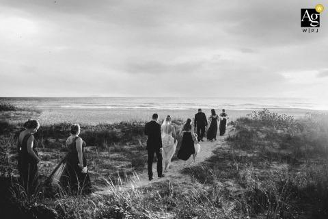 Regardez cette image de mariage pittoresque d'Anna Maria Island dans BW de la fête nuptiale marchant jusqu'à la plage montre la scène de cette célébration de couples, qui était une image vedette parmi les meilleures photographies de mariage en Floride de la WPJA