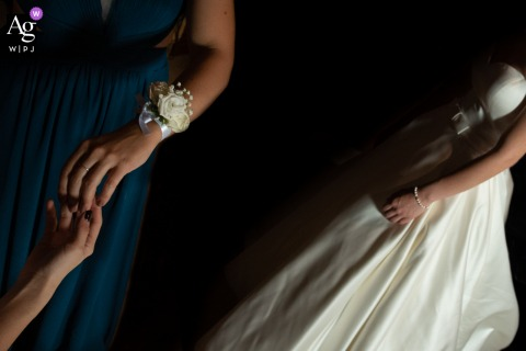 View thiselegant Moglia wedding image showing The florist has just finished putting the bracelet on the bridesmaids wrist, which was a featured pictureamong the best wedding photography in Mantova from the WPJA