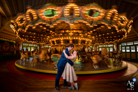 View thisgrand Glen Echo Park wedding day portrait of The couple embracing in front of a spinning carousel, which was a featured pictureamong the best wedding photography in Maryland from the WPJA