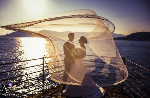 View thispicturesque Lerici wedding day Veiled portrait of the couple by the lake, which was a featured pictureamong the best wedding photography at Golfo dei Poeti in La Spezia from the WPJA