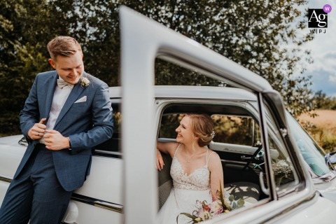 View thispictorial Hattingen Portraits of the bride and groom with a small vintage car, which was a featured pictureamong the best wedding photography at the Landhaus Siebe from the WPJA