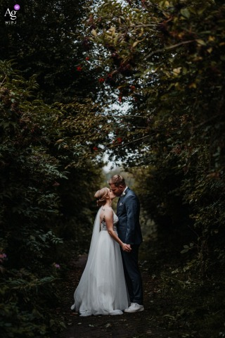 View thispoetic Hattingen Romantic Portrait of the bride and groom outdoors under the tall trees, which was a featured pictureamong the best wedding photography at the Landhaus Siebe from the WPJA