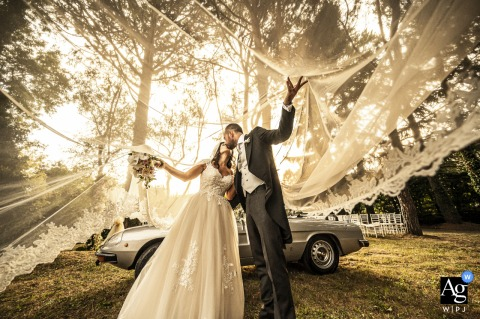 View thisgraceful Castello di Pomerio image of a sweet kiss under the veil by the vintage car, which was a featured pictureamong the best wedding photography from the WPJA
