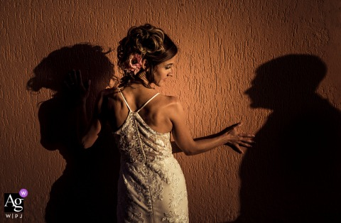 View thisdramatic La Spezia wedding image of the bride, using a shadow portrait of the groom, which was a featured pictureamong the best wedding photography in Teller, Lerici from the WPJA