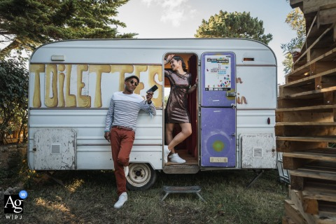 View thispoetic Quiberon wedding image of A couple in front of the portable trailer toilets, which was a featured pictureamong the best wedding photography in France from the WPJA