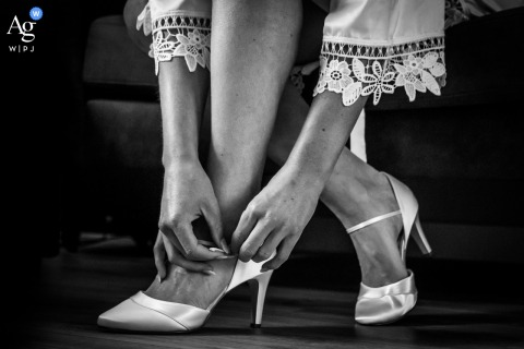 View thisornamental Netherlands wedding image in BW of The bride putting her shoes on, which was a featured pictureamong the best wedding photography from the WPJA