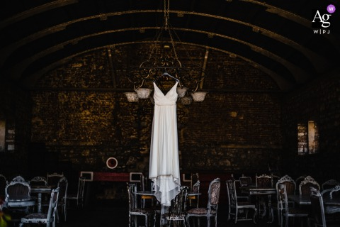 View thiselegant Izmir wedding image of a Bridal gown hung in an old restaurants chandelier, which was a featured pictureamong the best wedding photography in Turkey from the WPJA