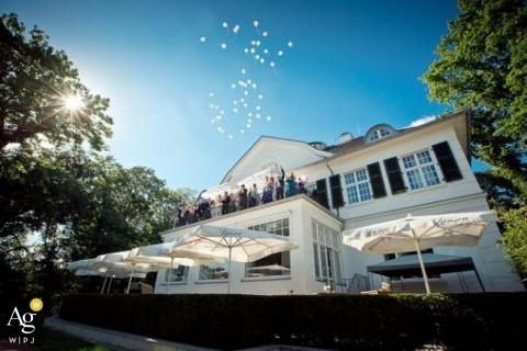 Fotografia ślubna w Hamburgu | Obraz zawiera: ujęcie szczegółowe, przyjęcie weselne, balkon, zwolnienie balonu, słońce