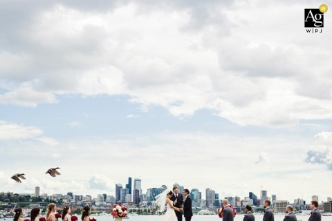 Seattle Creative Wedding Photojournalist| Image contains: bride, groom, ceremony, waterfront, city, sky, birds, wedding guests, bridesmaid, groomsmen
