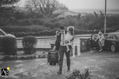 Waterford Artistic Wedding Reportage Photography | Image contains: black and white, bouquet, child, rain, getting ready, groom, carseat