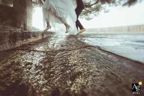Fotografia ślubna w Ankonie | Obraz zawiera: ujęcie szczegółowe, panna młoda, pan młody, stopy, buty, kałuża, ulica