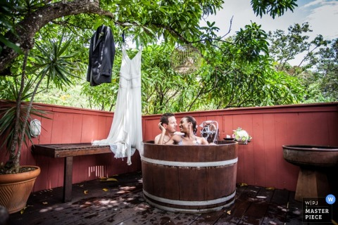 Miami bride and groom sit in hot tub with their tux and dress hanging next to them - Florida wedding photo