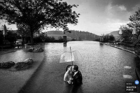 De bruid en de bruidegom van Milaan bevinden zich in een pool in de regen met de paraplu - het huwelijksfotografie van Lombardije