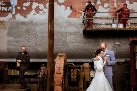 Mariage des jeunes mariés de Rotterdam embrassant un portrait le jour du mariage alors que des ouvriers peignent derrière eux - Photojournaliste de mariage en Hollande du Sud