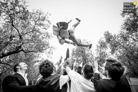 De bruidegom die van Milaan in de lucht door gasten wordt geworpen - het huwelijksfoto van Lombardije
