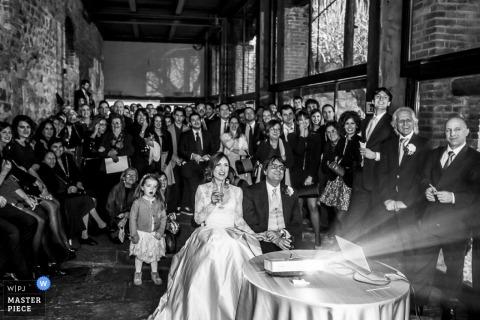 Bruid en bruidegom van Lecco en gasten kijken naar een video bij de receptie - Bruiloftfotojournalistiek in Lombardije