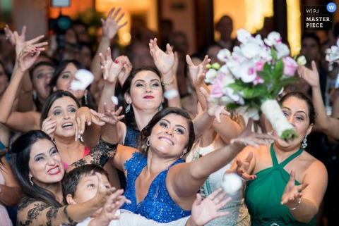 Minas Gerais guests reach for the bouquet at the reception | Brazil wedding photography
