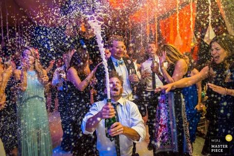 De bruidegom van San Diego opent een fles champagne rond gasten Californië trouwfoto