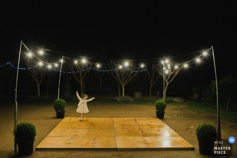 New South Wales girl dancing alone at the reception outdoors under lights at night - Australia wedding photography