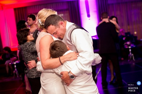 Nova Scotia bride and groom hug boy while they are dancing - Canada wedding photojournalism