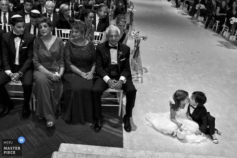 San Diego jongen en meisje kus in het midden van het gangpad bij de huwelijksceremonie   California wedding photojournalism