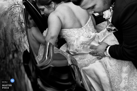 Lake Tahoe groom helping the bride get in the car with her dress - California wedding photojournalism