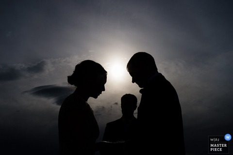 Lake Tahoe bride and groom silhouetted during the outdoor ceremony as the sun is setting - California wedding photo