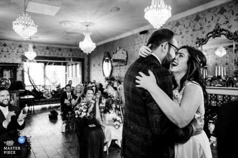 Hertfordshire bride and groom hug and laugh at the wedding ceremony - England wedding reportage photo