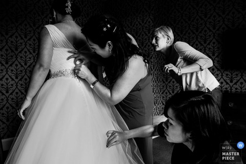 Bristol bridesmaids helping the bride get her dress ready for the wedding | England wedding reportage photo