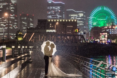 Photo of a bride and groom standing together on a rainy bridge shielding themselves with an umbrella by a Taipei, Taiwan wedding photographer.