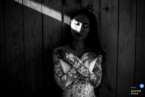The bride crosses her arms over her chest as a beam of light shines over her eyes in this black and white portrait composed by a Germany wedding photographer.