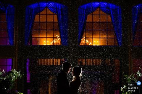 Foto en blanco y negro de una novia y un novio de pie afuera en la noche mientras la nieve cae a su alrededor por un fotógrafo de bodas de Nueva Jersey.