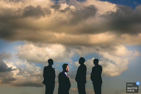 Photo of four men standing against a backdrop of blue skies and clouds by a Derbyshire wedding reportage photographer.