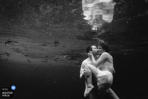 A groom kisses his bride underwater in this black and white image created by a Cartago, Costa Rica documentary wedding photographer.