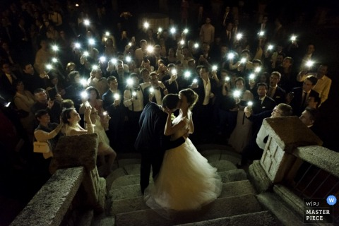 Photo of the bride and groom kissing on stone steps as the guests carry candles by a Lombardy wedding photographer.