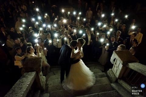 Foto de la novia y el novio besándose en los escalones de piedra mientras los invitados llevan velas de un fotógrafo de bodas de Lombardía.
