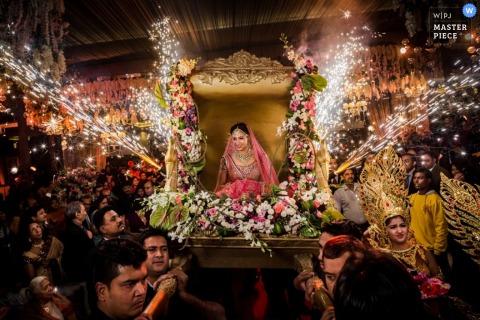 Foto van de bruid die in een palankijn wordt gedragen die door bloemen en sterretjes door een het huwelijksfotograaf van Montpellier wordt omringd.
