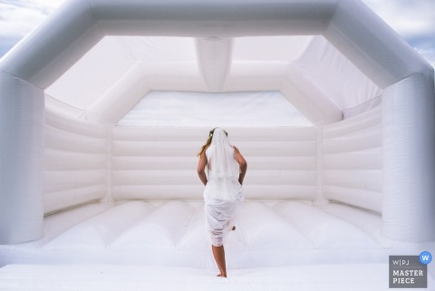 Foto van de bruid die in een wit springhuis stapt door een fotograaf van een huwelijksreportage in Londen, Engeland.