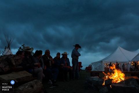 Zdjęcie gości stojących wokół ogniska z namiotem recepcyjnym w tle przez fotografa ślubnego Missoula, MT.