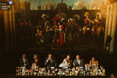 The bride, groom, and their parents sit together during the reception in front of an ornate painting in this image created by a Greater Manchester, England wedding reportage photographer.